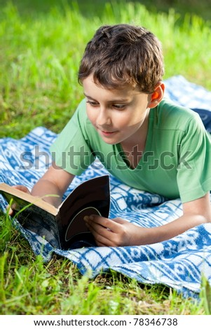 Portrait of a boy reading a book outdoor on the grass - stock photo