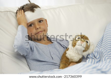 Portrait of a boy showing the bandage on his forehead - stock photo