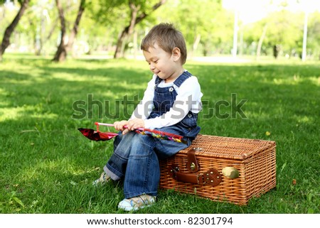 Portrait of a boy sitting on the basket in the park - stock photo