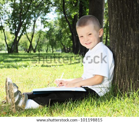 Portrait of a boy sitting with a book in the park