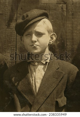Portrait of a boy smoking,'A.M. Monday, newsies at Skeeter's branch They were all smoking.', St. Louis, Missouri, photograph by Lewis Wickes Hine, May 9, 1910