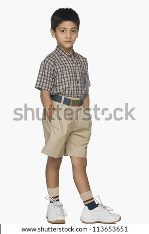 Portrait of a boy standing with his hands in pockets - stock photo