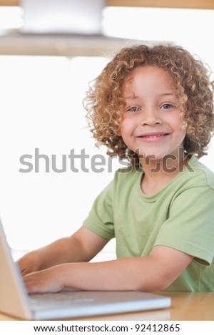 Portrait of a boy using a notebook in a kitchen - stock photo
