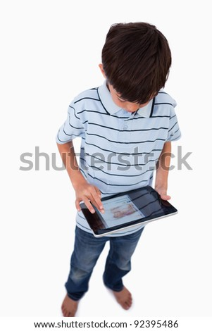 Portrait of a boy using a tablet computer against a white background
