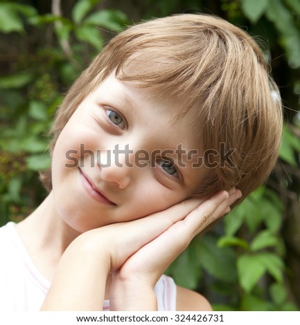 Portrait of a Boy with Blond Hair Looking Outdoors - stock photo