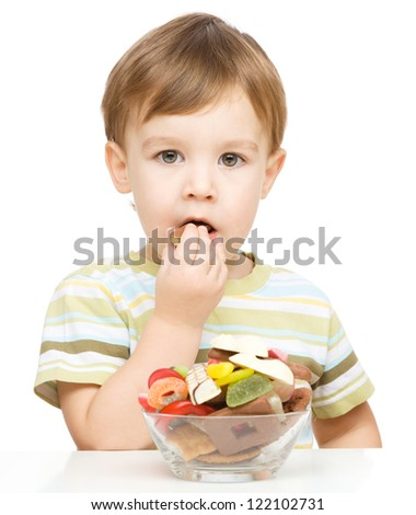 Portrait of a boy with candies, isolated over white