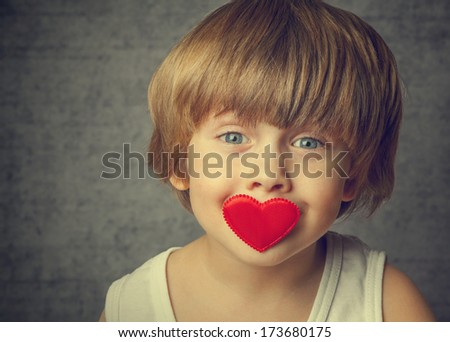 Portrait of a boy with hearts on face - stock photo
