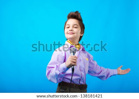 portrait of a boy with microphone on the blue background - stock photo