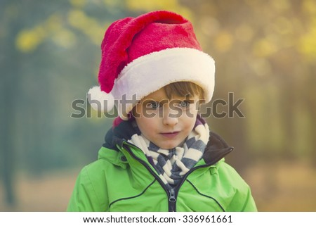 portrait of a boy with Santa hat in park in the fall
