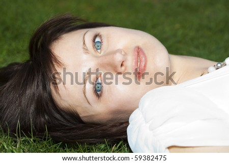 portrait of a bride lying on the grass - stock photo