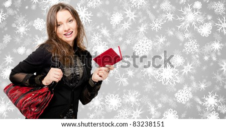 Portrait of a bright beautiful young woman with fashion handbag preparing for boxing day and christmas - buying gifts from gift-list. Lots of copyspace. Background with snowflakes
