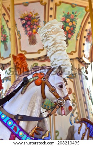 Portrait of a brightly decorated carousel pony with plumage headgear. - stock photo