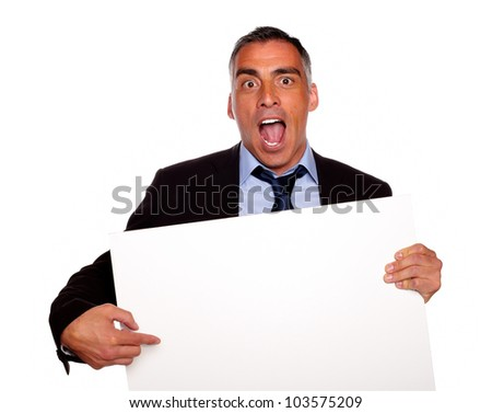 Portrait of a broker screaming, pointing and holding a white card with copyspace on isolated background - stock photo