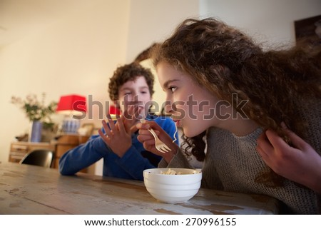 Portrait of a brother and sister sitting at dining room table eating food - stock photo