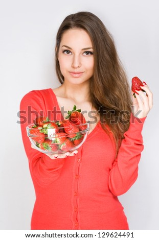 Portrait of a brunette beauty offering bowl of strawberries, selective focus on the bowl. - stock photo