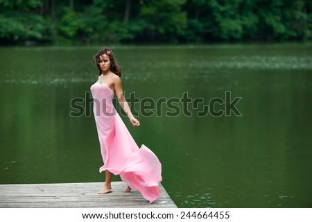 Portrait of a brunette beauty standing by the water - stock photo