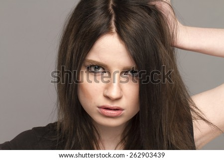 Portrait of a brunette emotions. beautiful girl in the studio on a gray background depicts different emotions