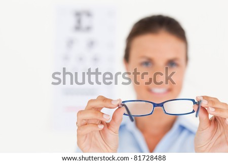 Portrait of a brunette eye specialist handing out glasses smiling into the camera in her surgery - stock photo