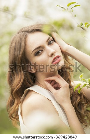 Portrait of a brunette girl in the garden, close up shot - stock photo