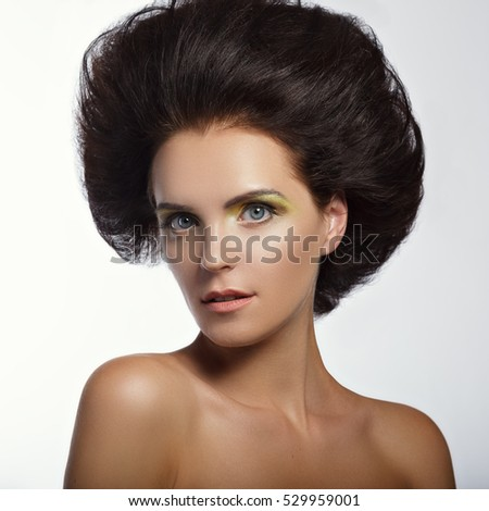 Portrait of a brunette with fluffy hair. On a light gray background.Yellow make up. Close up. Foursquare