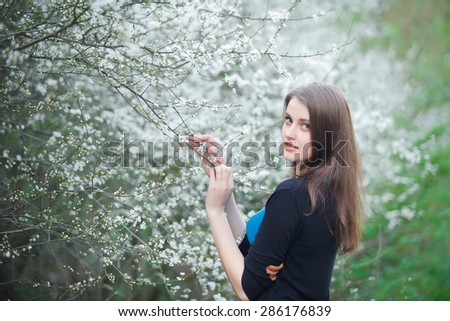 Portrait of a brunette woman inhales the scent of flowers_horizontal