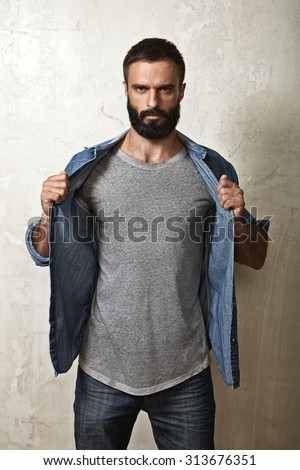 Portrait of a brutal bearded guy wearing grey t-shirt - stock photo