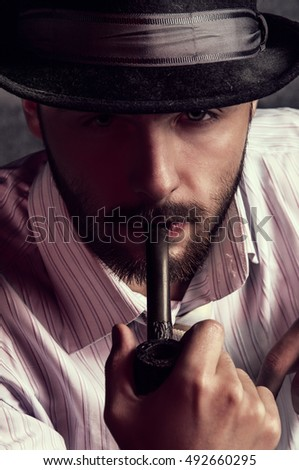 Portrait of a brutal man with a pipe