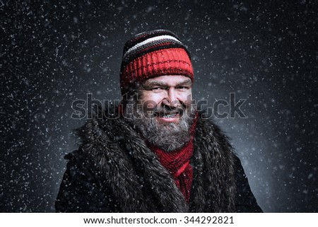 Portrait of a brutal mature man clothed in winter clothes with snowflakes - stock photo