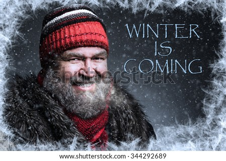 """Portrait of a brutal mature man clothed in winter clothes with snowflakes, hoarfrost and text """"WINTER IS COMING"""" - stock photo"""
