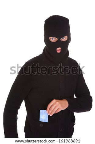 Portrait Of A Burglar Putting Credit Card In His Pocket - stock photo