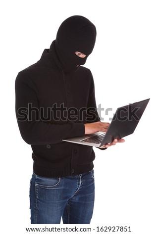 Portrait Of A Burglar Using Laptop Isolated On White Background - stock photo