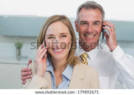 Portrait of a business couple using cellphones in the kitchen at home - stock photo