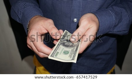 Portrait of a business man holding money, isolated on black.