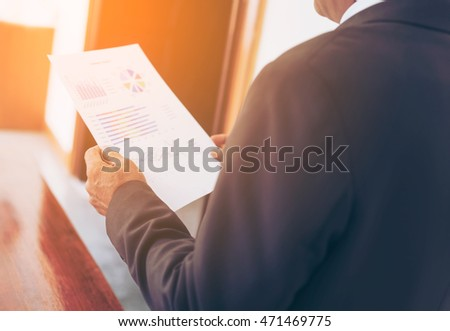 Portrait of a business man looking at invoice paper in office morning light.