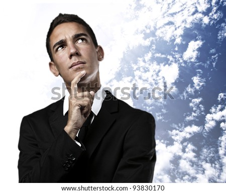 portrait of a business man thinking against a cloudy sky background