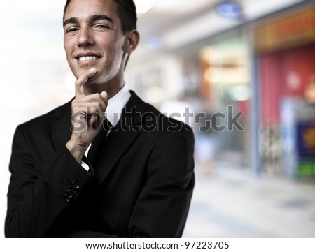 portrait of a business man thinking against a crowded place - stock photo