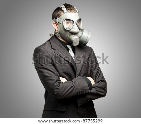 portrait of a business man with gas mask over grey background - stock photo