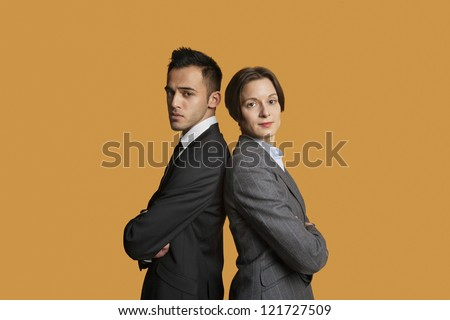 Portrait of a business partners standing back to back with arms crossed - stock photo