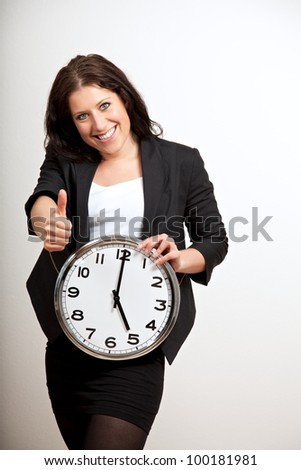 Portrait of a business professional giving a thumbs up sign while holding a clock
