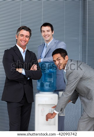 Portrait of a business team filling cup from water cooler in the office