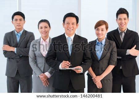 Portrait of a business team standing and posing at camera