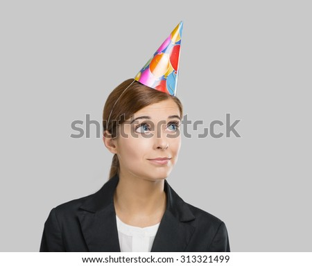 Portrait of a business woman celebrating something with a birthday hat on the head - stock photo