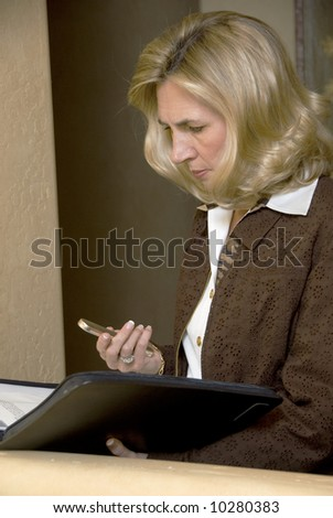 portrait of a business woman checking her mobile phone - stock photo