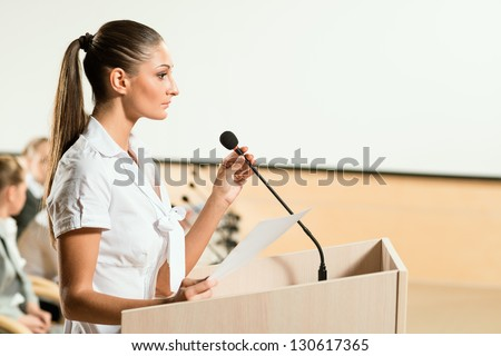 Portrait of a business woman holding a microphone and looks ahead - stock photo