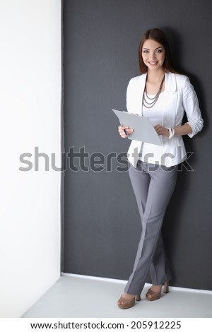 Portrait of a business woman holding folder , Isolated on grey background - stock photo