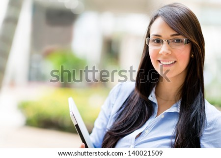 Portrait of a business woman holding laptop computer - stock photo