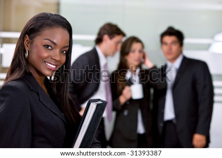 Portrait of a business woman in an office smiling - stock photo