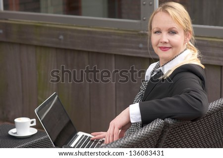 Portrait of a business woman relaxing with laptop and cup of coffee outdoors - stock photo