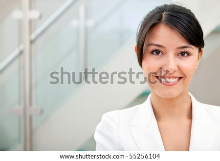 Portrait of a business woman smiling at the office - stock photo