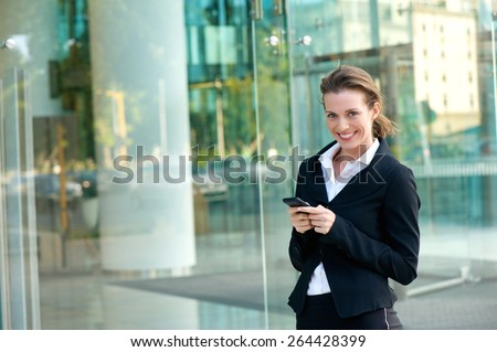 Portrait of a business woman smiling with cell phone outside office building - stock photo